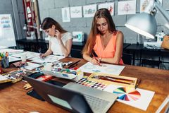 Designers workspace. Two female artists drawing decorative elements sitting at desk in creative studio stock image