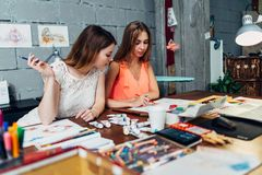Designers workspace. Two female artists drawing decorative elements sitting at desk in creative studio royalty free stock image