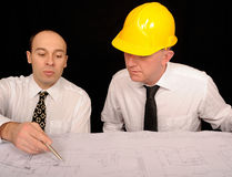 Designing Engineers. A portrait of two engineers discussing a construction plan, on a black studio background Stock Image