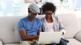 Designteam, das auf der Couch arbeitet an Laptop sitzt stock video footage