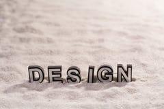 Designwort auf weißem Sand lizenzfreie stockfotos