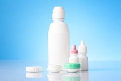 Desinficera lösningen för kontaktlinser och ögondroppar på blå bakgrund Fotografering för Bildbyråer