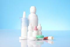 Desinficera lösningen för kontaktlinser och ögondroppar på blå bakgrund Arkivbild