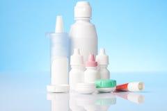 Desinficera lösningen för kontaktlinser och ögondroppar på blå bakgrund Royaltyfri Fotografi