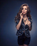 Desirable. A model female dressed in a Camoflage Pattern jacket, denim shorts and black stylish necklace on isolated dark blue royalty free stock images