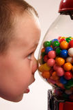 Desire. A young boy looks with longing into a gumball machine full of sweets