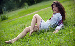Desire. Portrait of a young sexually girl in the national shirt lying on the grass Royalty Free Stock Photography