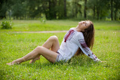 Desire. Portrait of a young sexually girl in the national shirt lying on the grass Royalty Free Stock Photo