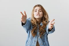 Desire blinded everything. Portrait of longing impratient attractive woman with blonde hair, wearing denim jacket. Biting lip, pulling hands towards camera Stock Photo