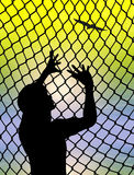 Desire for Freedom. Desperate prisoner or refugee behind a fence longing for to live a free life stock illustration