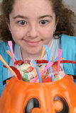 Desire for Halloween Candy. A young girl looking longingly at a bucket full of halloween candy royalty free stock photos