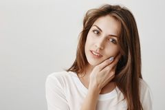 Desire and sensuality concept. Portrait of charming european woman tilting, gently touching cheek and gazing at camera. Flirting or expressing affection Stock Images