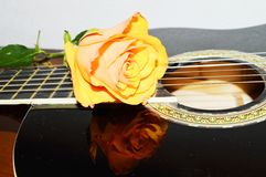 Desire song. Beautiful yellow rose on a black guitar, suggesting desire for love royalty free stock photography