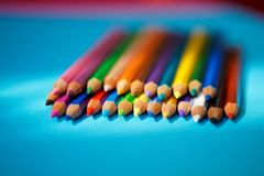 Sharpened colored pencils lie on a blue background in the sun`s rays royalty free stock photos