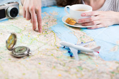 Desire to travel. A woman sitting at table with a map with a paper airplane, compass and camera and visualises his desire to travel. Shallow depth of field Royalty Free Stock Photo