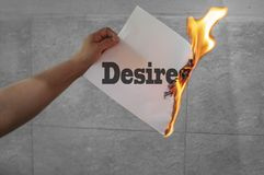 Desires text on fire on paper. With hand royalty free stock photography