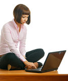 On a desk. Beautiful girl sits on a desk with a laptop Stock Image