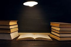 Desk against the background of the chalk board, books in the dark under the light of a lamp. Copy space. Desk against the background of the chalk board, books in stock image