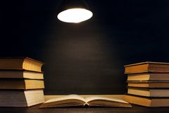 Desk against the background of the chalk board, books in the dark under the light of a lamp. Copy space.  stock image