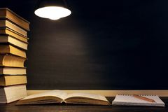 Desk against the background of the chalk board, books, notebook and pens, in the dark under the light of a lamp. Copy space.  stock photo