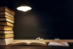 Desk against the background of the chalk board, books, notebook and pens, in the dark under the light of a lamp. Copy space.  stock images