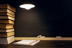 Desk against the background of the chalk board, books, notebook and pens, in the dark under the light of a lamp. Copy space.  stock photography