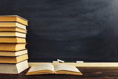 Desk against the background of chalk boards and books. Copy space.  royalty free stock image