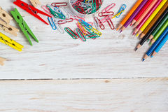 Desk of an artist. Colorful pencils and paperclips on the white wooden table background stock photography