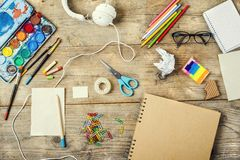 Desk of an artist. With lots of stationery objects. Studio shot on wooden background stock photography