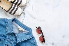 Desk of beauty blogger with trendy jeans jacket, fashionable striped sandals, retro fashioned women`s sunglasses on marble backgro stock image