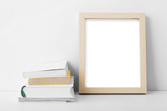 Desk blank photo frame nest to stack of books Royalty Free Stock Photo
