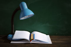 Desk blue lamp, open notebook and colored pencils against a school green board. Stock Photos