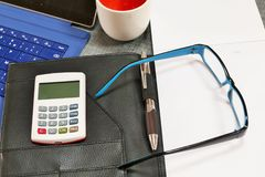 Desk with a calculator glasses, notepad and coffee. Stock Photos