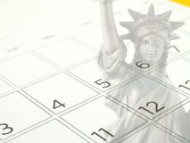 Close-up white desk calendar with days and dates in July 2017 and part of faded bronze metal Statue of Liberty. Independence Day (American national day&#x29 royalty free illustration