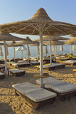 Desk chairs and umbrella on a beach. Deck chairs under an umbrella on a beach in the hot afternoon sun Stock Photos