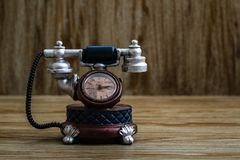 Desk Clock with Antic Telephone Shape on Brown Background. Desk clock with antic telephone shape on brown wooden background Royalty Free Stock Photography