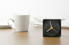 Desk clock and cup and newspaper Royalty Free Stock Photography