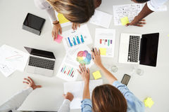 Desk and colleagues at a business brainstorm, overhead view Royalty Free Stock Photography