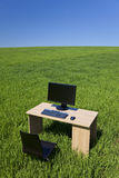 Desk and Computer In Green Field With Blue Sky Royalty Free Stock Image