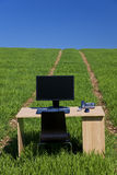 Desk and Computer In Green Field With Path Stock Photography