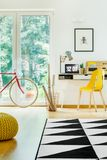 Desk with computer in room. Rolls of paper in basket next to yellow chair at desk with computer in room with geometric carpet and bike royalty free stock photography