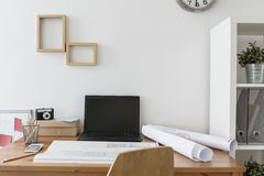 Desk in the creative office. With laptop and architects plan Royalty Free Stock Image