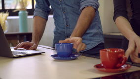 Desk with cups near stand male and female unvisible. Man and woman hands taking cup with tea or coffee. On the wooden table two mugs red and blue and laptop stock footage