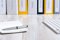 Desk of decision maker. Side view on light wooded desk with pen, stylish leaver note pad and keyboard, with stack of folders on the background Royalty Free Stock Images