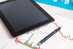 Desk with digital tablet. Marketing Research. Desktop in stock exchange office with a tablet pc showing stock market chart Royalty Free Stock Photography