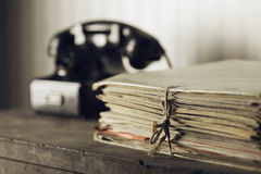 Old phone on a desk with documents Stock Photo
