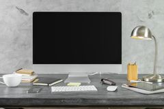 Desk with empty pc monitor front. Close up and front view of hipster desk with empty pc monitor, various other devices, coffee cup and objects on concrete wall Royalty Free Stock Image
