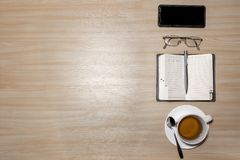 Desk with eyeglasses, notepad, smartphone, pen and a cup of tea on a wooden table. Top view with copy space. Flat lay - image.  royalty free stock images