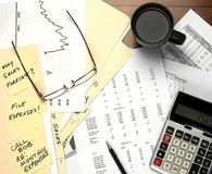 Desk with financial papers, calculator, coffee cup Stock Photo