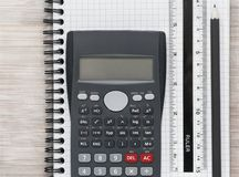 Desk flat lay with calculator, ruler and pencil on a notebook stock image